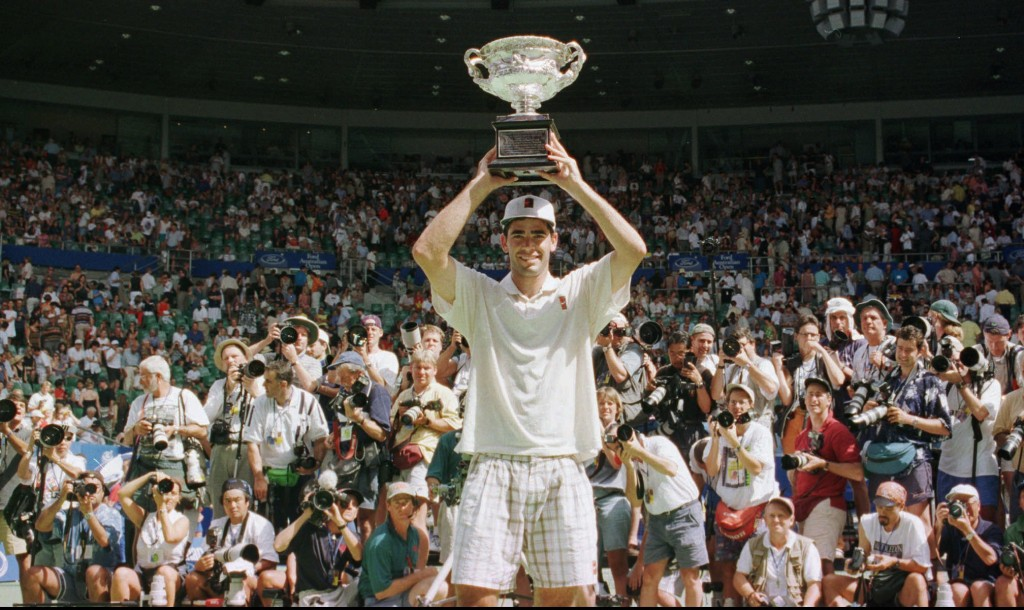 Pete Sampras from Tampa, Fl, USA holds his trophy above his head in front of a mass of photographers after he won the final of the  Australian Open Tennis Championships in Melbourne, Sunday, January 26, 1997. Sampras defeated Carlos Moya of Spain 6-2, 6-3, 6-3, to win the tournament. (AP Photo/Russell McPhedran)