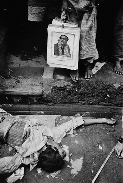 "A corpse and a poster of Sheikh Mujibur Rahman, the person responsible for the uprising of Bangladesh: ""...Once 50000 people lived here. Now there were only 200...the rest have fled, leaving the dead on the street..."" - Kishor Parekh, Bangladesh War 1971."